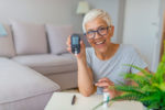 woman holding diabetes testing unit Your Insurance Gal